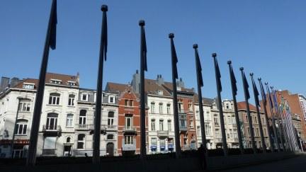 Direkt neben den hohen Glasfassaden zeigen kleinere, bunte historische Häuser, dass man sich tatsächlich in Belgien befindet.